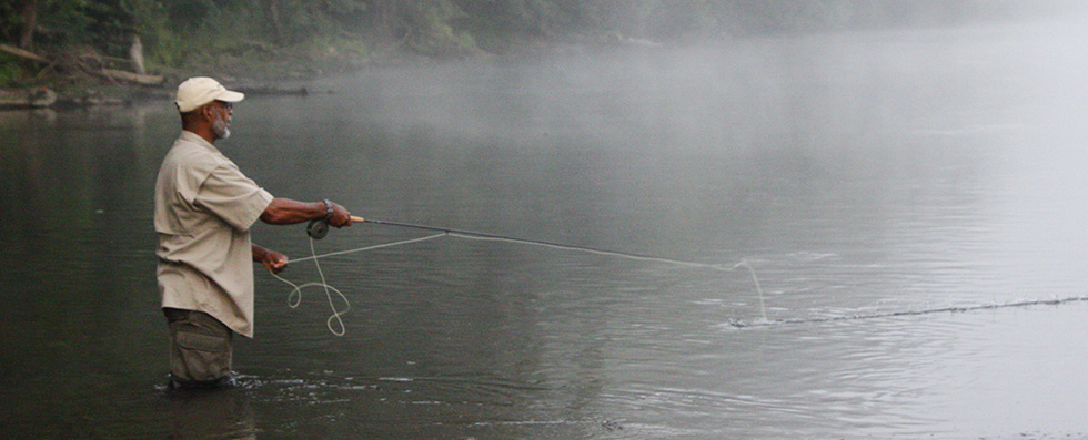 man flyfishing on river