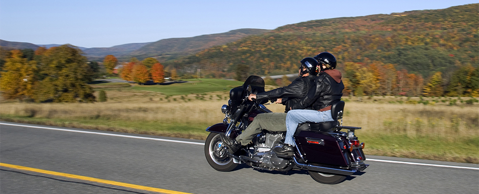 two people riding motorcycle on mountain road