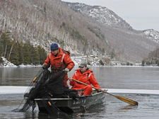 DEC wildlife technicians tend a trapnet on an icy lake