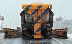 A plow truck spreading salt and sand
