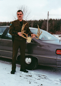 An ECo standing by a car holding a pair of shed antlers
