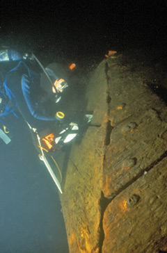 A diver inspects the hull of an underwater shipwreck