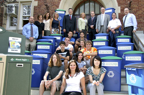 A group of students and teachers pose on the front steps of their school with new recycling bins
