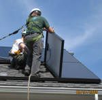 A solar panel installer on a roof with some solar panels
