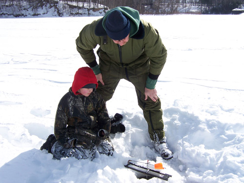 A father and son watching their tip up while ice fishing