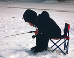A young boy with a jigging rod sitting by his ice fishing hole