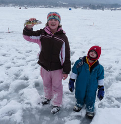 A little girl holding a fish and a little boy standing on a frozen lake