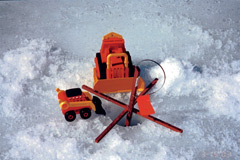 An ice fishing tip up with orange plastic kids toys around the hole