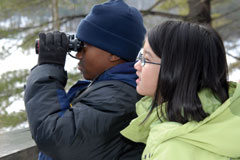 A young boy, with binoculars, and a young girl look for birds
