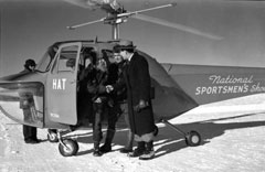 Rondeau steps from a helicopter onto a snowy field, shaking hands with a man in a long coat.