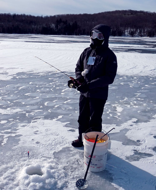 A bundled-up person is fishing through a hole in the ice on a lake
