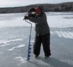 A woman drilling a hole through the ice with an auger for ice fishing