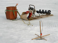 Ice fishing gear including an ice auger, tip-up, sled and creel