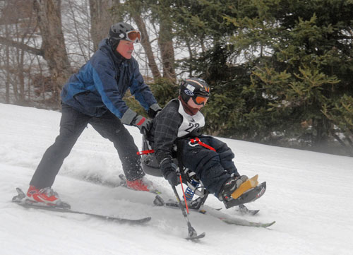 A man on skis guides another skier using adaptive ski equipment down the slope