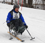 A person skiing with special adaptation for those with physical disabilities