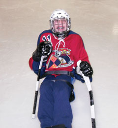 A boy in a helmet and red and blue hockey gear holds adaptive hockey sticks