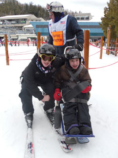 A ski instructor and two ski students, one on regular skis, the other on a bi-ski