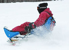 A person riding a special adaptive sled.