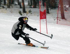 A skier with one leg skis down a hill with one ski and two crutches with mini-skis attached