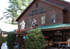 An Adirondack store with a canoe and two fake canoers on its porch roof
