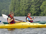 Two girls in life vests paddling kayaks
