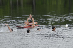 A group of swimmers in a lake overseen by a lifeguard.