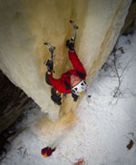A man in a red jacket climbs up a frozen ice wall
