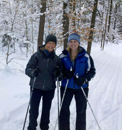 Two women wearing cross-country skis standing on a snowy trail in the woods
