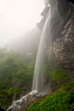 A tall waterfall viewed from the side on a misty day