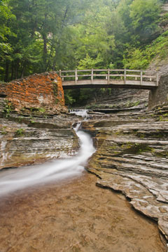 A waterfall flows under a wooden bridge spanning a rocky ravine
