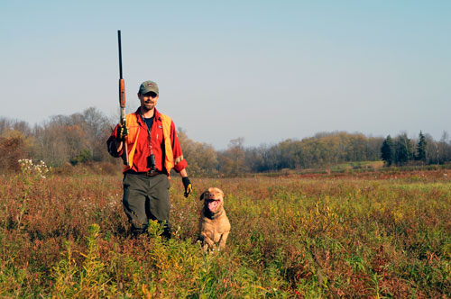 A hunter with a gun and a dog in a field