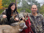 A young girl and her father pose with her buck