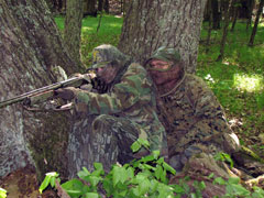 Two people in full camoflage, one pointing a rifle, sit at the base of some trees