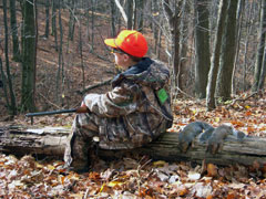 A boy wearing an orange cap and camoflage sits on a fallen tree holding his gun with two dead squirrels on the log behind him