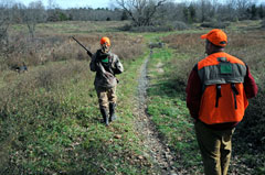 Two hunters follow a narrow path through a field