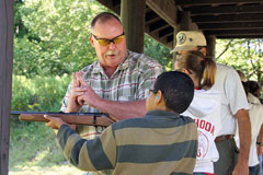 A hunter ed instructor helps a student at the firearms safety class