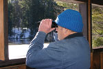 A man in a blue ski hat and holding binoculars looks out of a viewing platform