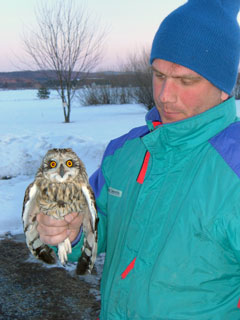 A man in a green and ble ski jacket holds a short-eared owl by the legs