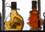 Two decorative glass bottles contain different grades of maple syrup