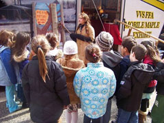 Schoolkids gather around an RV with a mobile maple exhibit