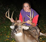 A young girl holds up the head of a large buck that she killed during youth firearms season
