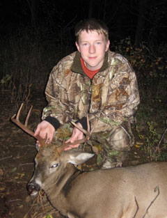 A young man in a camoflage jacket poses with an 8-point buck that he shot
