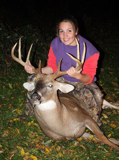 A young woman poses with a large buck that she shot