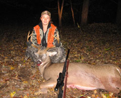 A girl in an orange vest poses next to her buck and shot gun