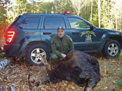 ECO John Blades in front of his partol car with the moose carcass