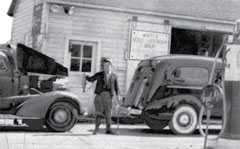 A 1941 black and white photo of Ed Bang standing at a gas station holding his prized rainbow trout