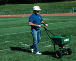 A groundskeeper using a spreader to apply ammendments on athletic fields