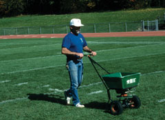 A man overseeding perennial rye grass on athletic fields