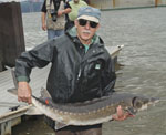 A man standing in the water holding a sturgeon