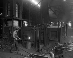 A man working a large industrial furnace at a mill